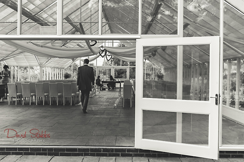 groom walking into glass house