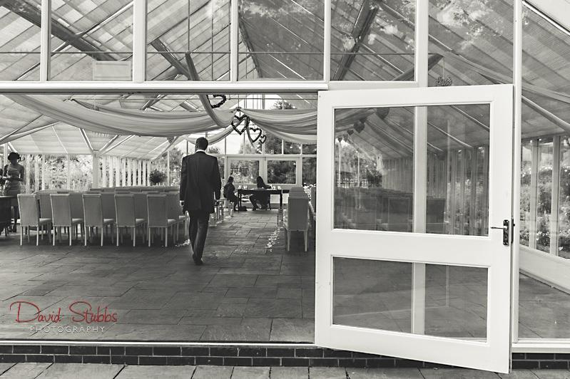groom walking into glass house