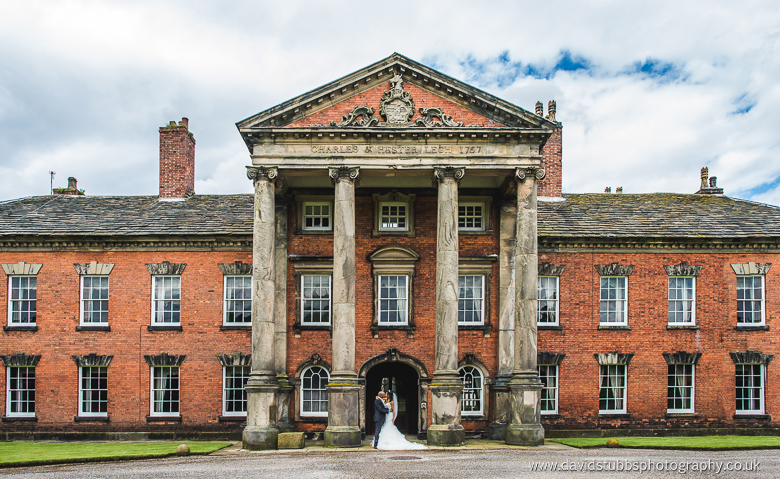 front of adlington hall wedding