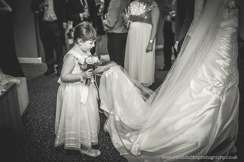 flwoer girl holding wedding dress