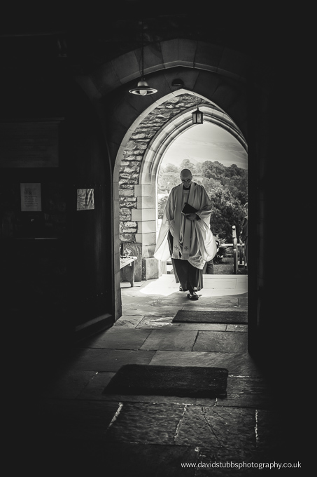 priest going through door black and white