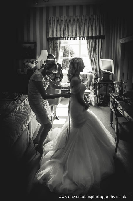 bride having dress put on