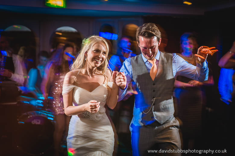 bride and groom holding hands dancing
