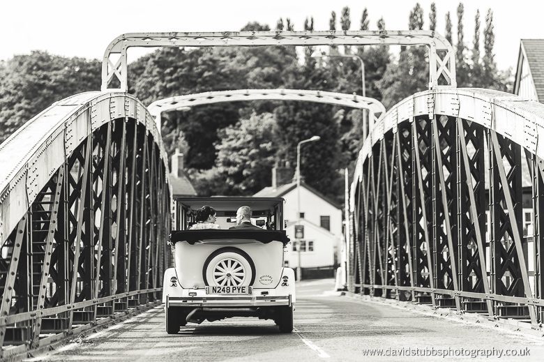 wedding car driving away over bridge