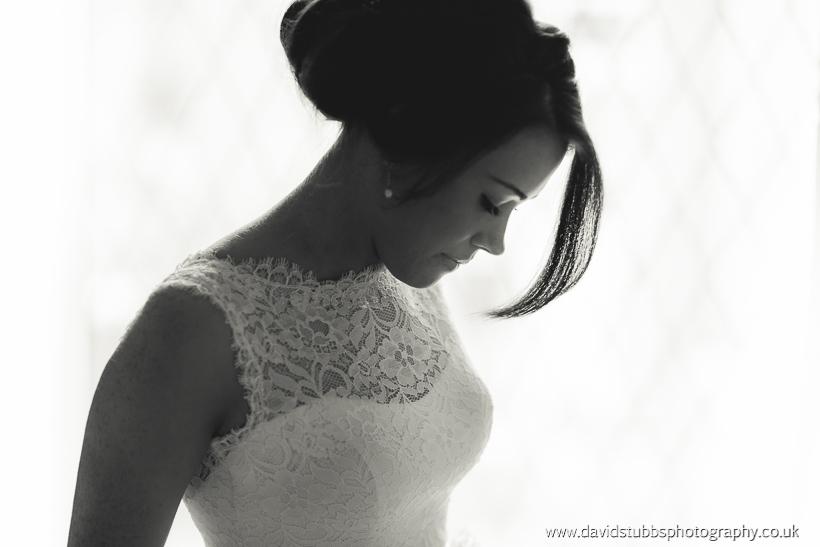 bride in dress stood by window