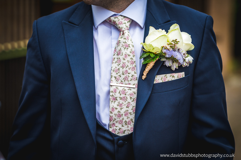 groom in suit with flowers