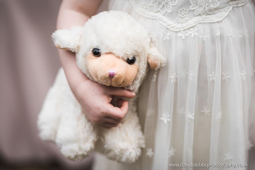 flower girl holding toy lamb