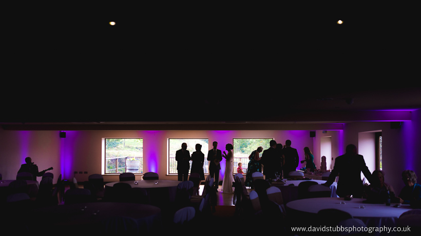 silhouette of wedding guests stood at window