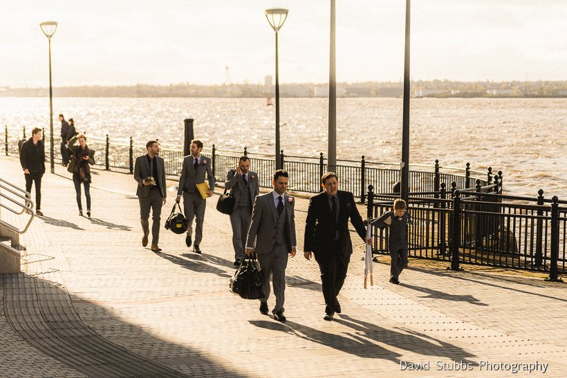 groom and friends walking through liverpool to wedding