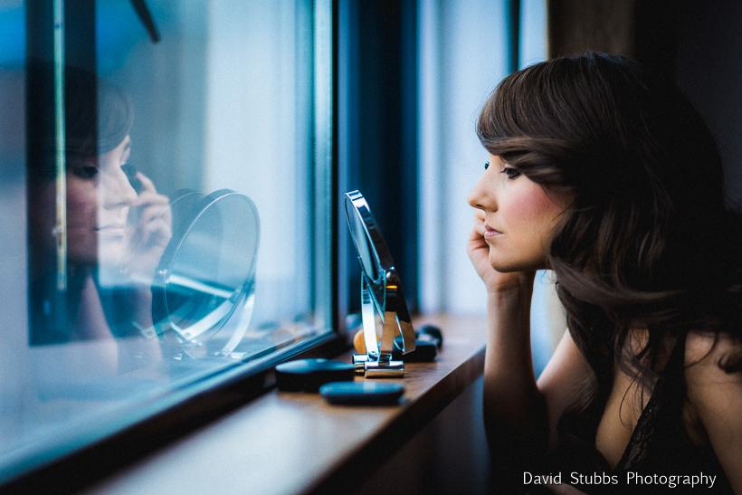 bride doing makeup in mirror