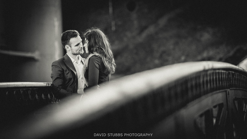 black and white photo of engaged couple on bridge