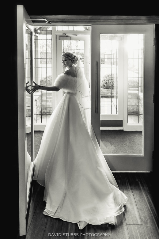 bride in dress by window