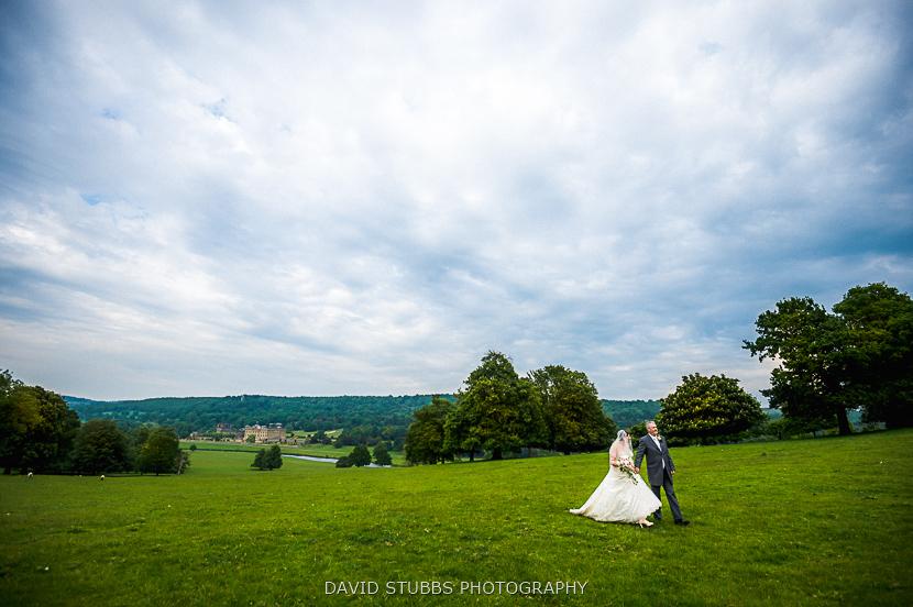 newly married couple walking in field