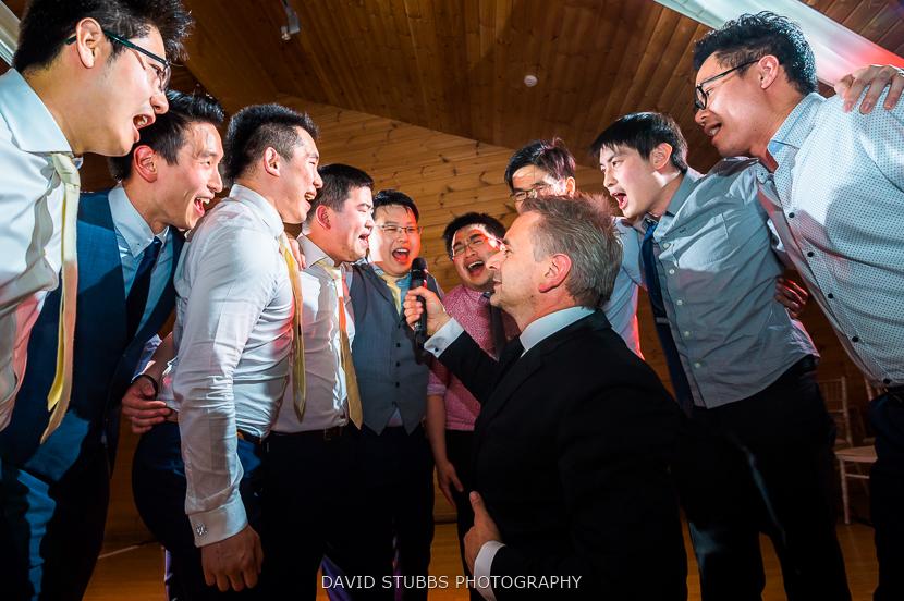 wedding singer giving groom microphone