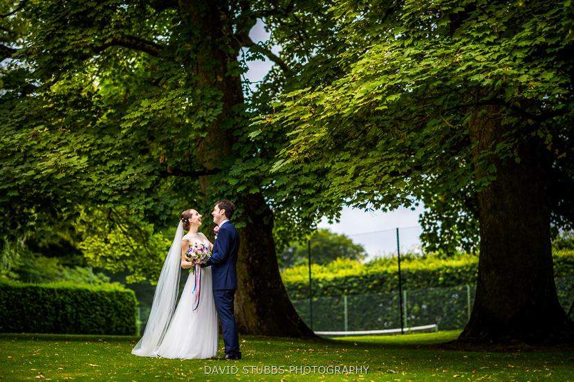 husband and bride stood under tree