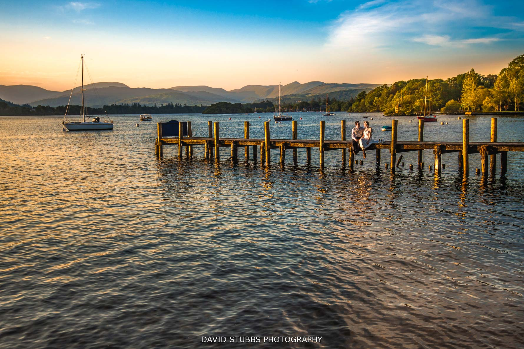 bride and groom sat by windermere