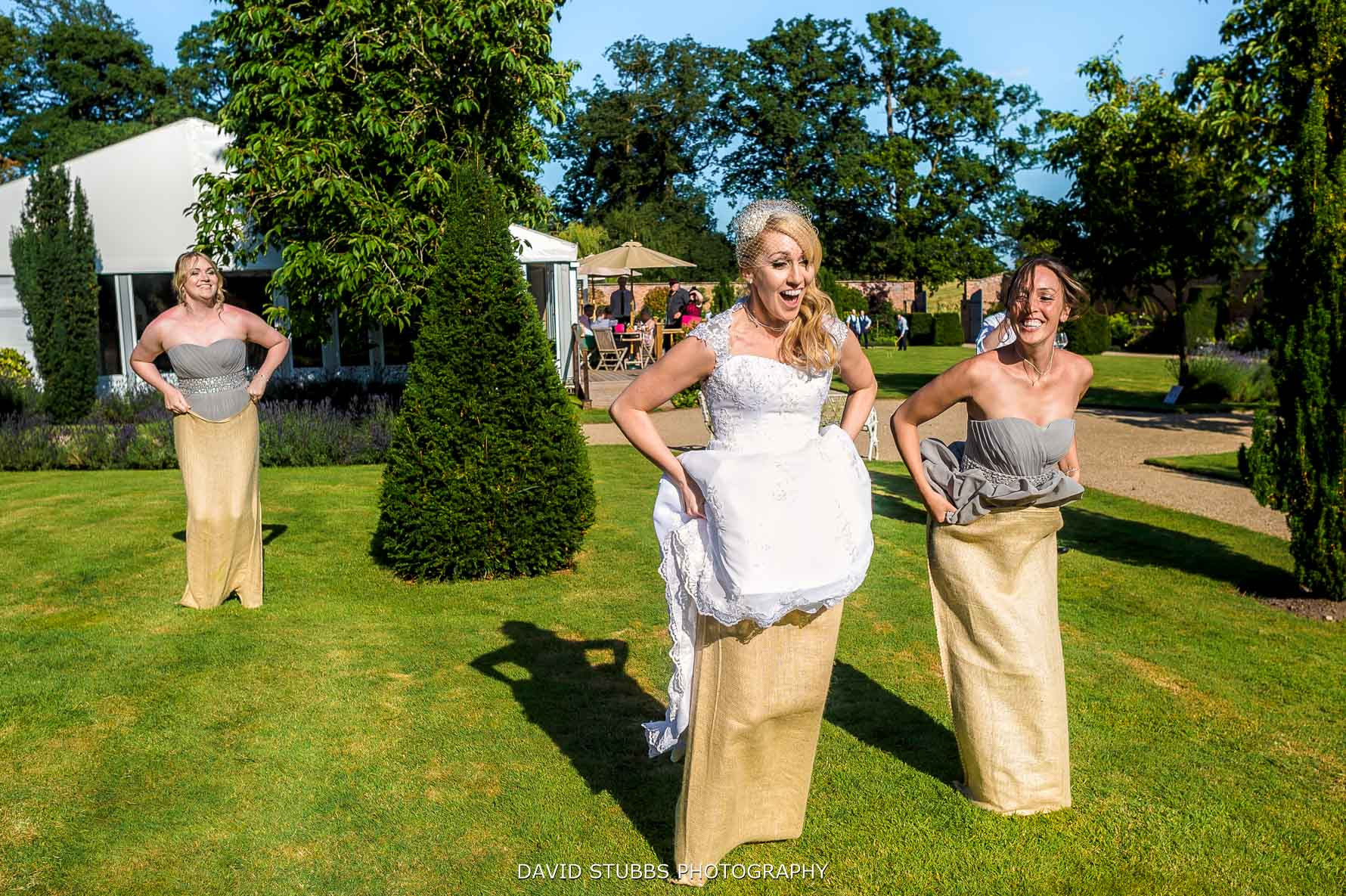 bride and bridemaids in a sack race