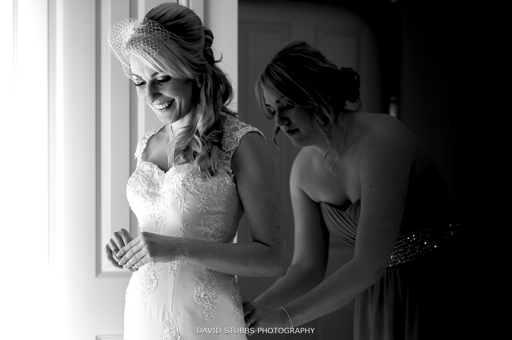 having her wedding dress done up by the window