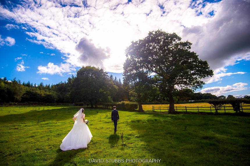 bride and groom walking off wedding woods