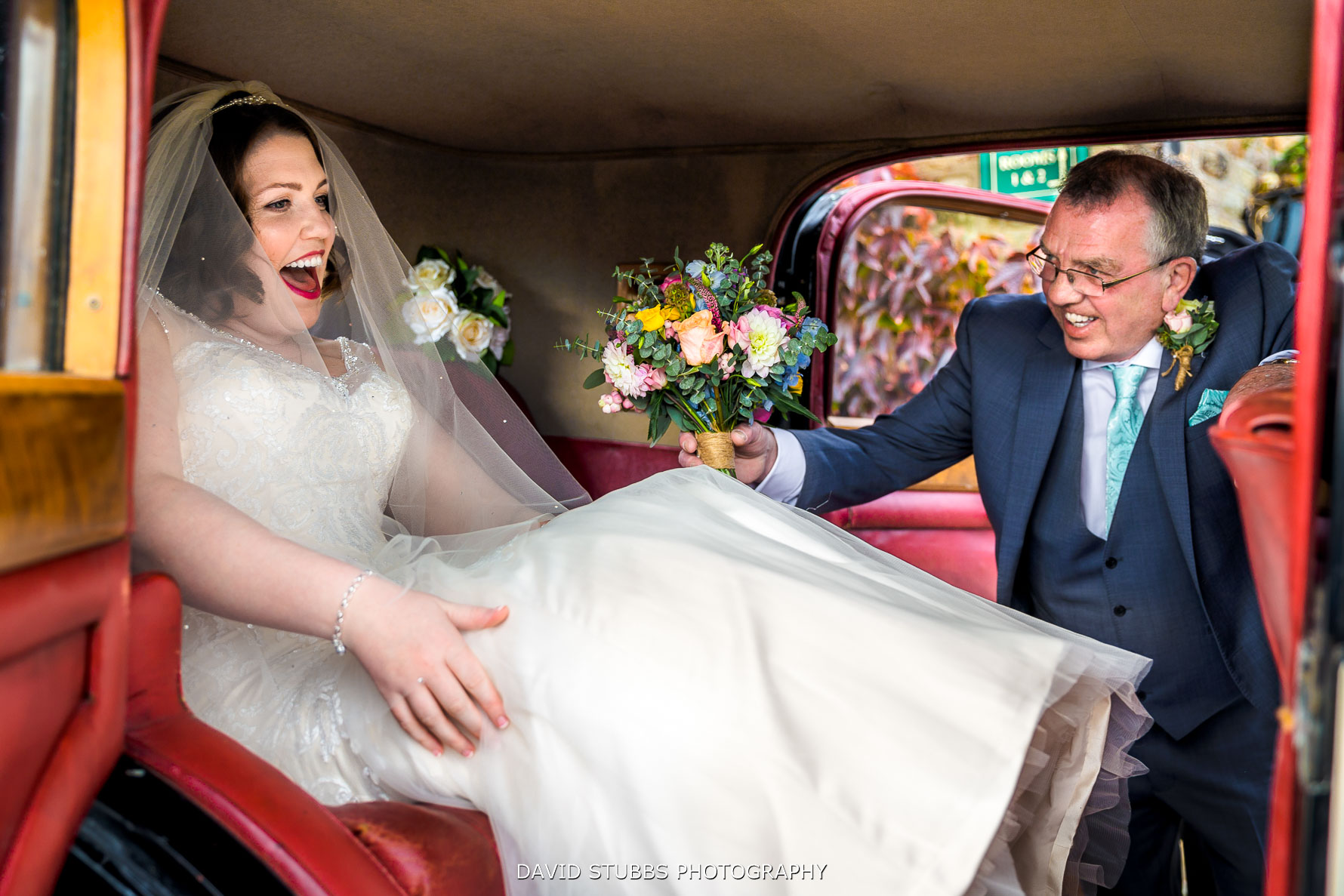 bride getting into the car with dad laughing