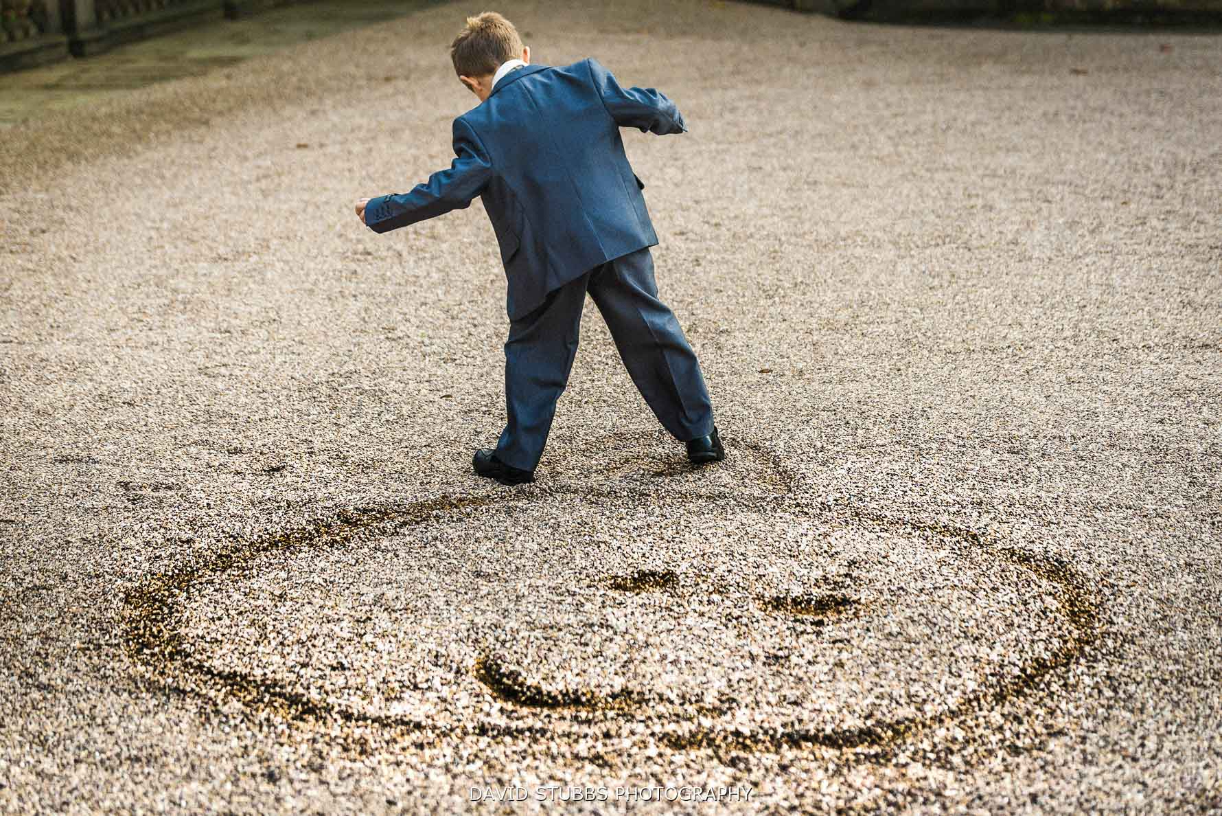 boy drawing a photo of a face in the gravel