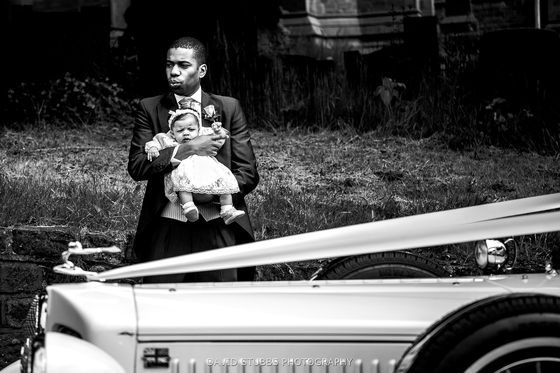 kid by wedding car black and white