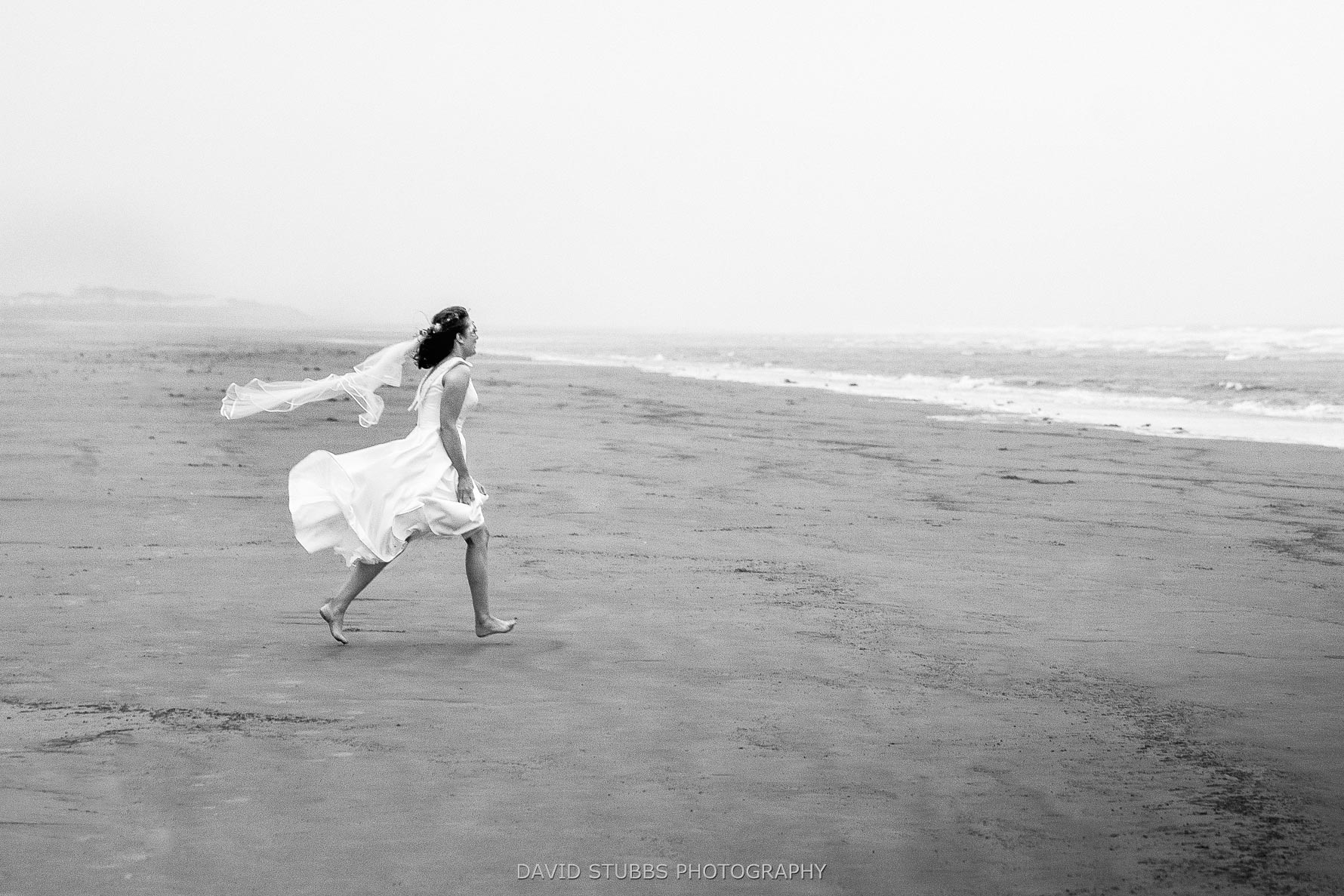 bride running towards the sea at the wedding