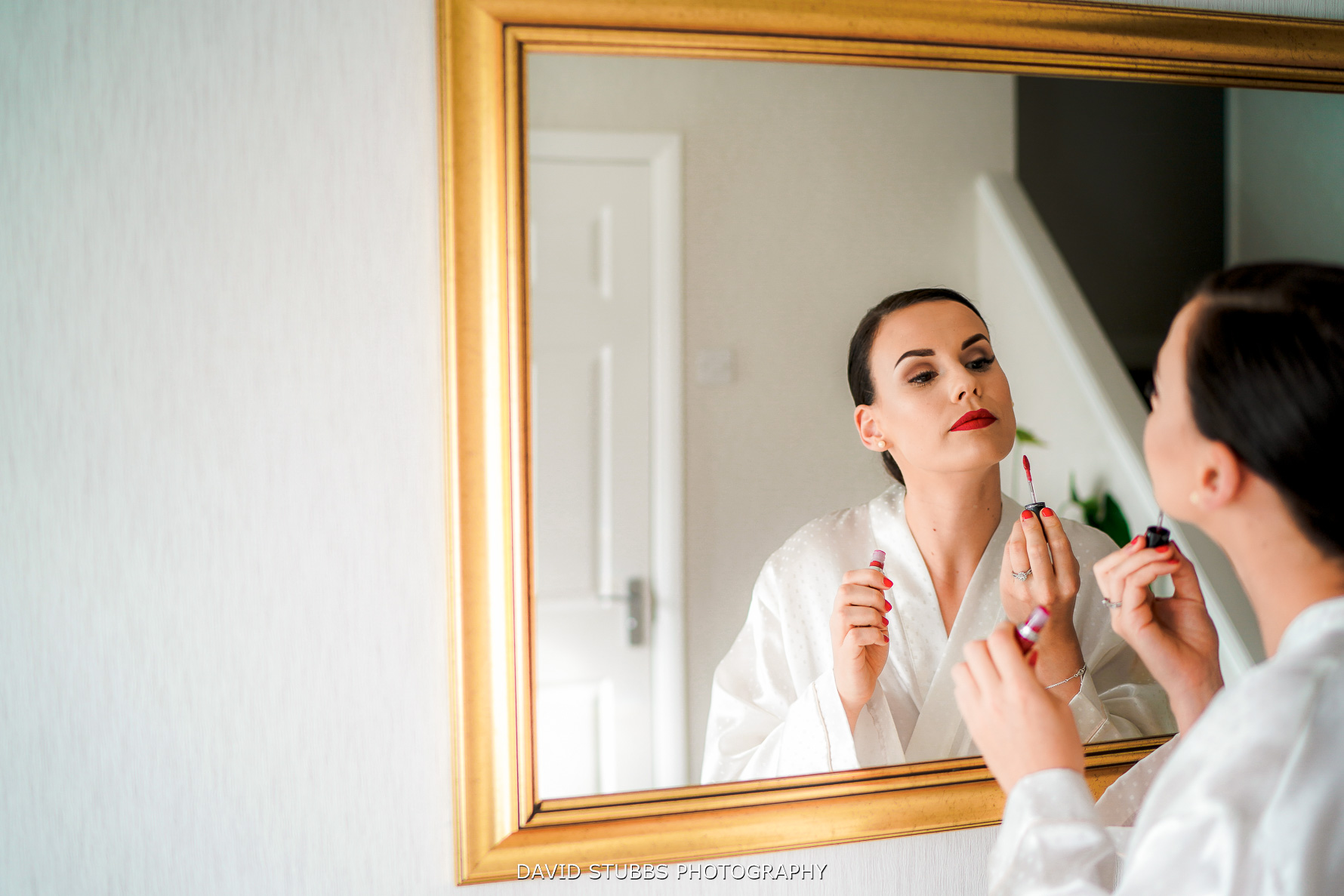 bride applying red lipstick