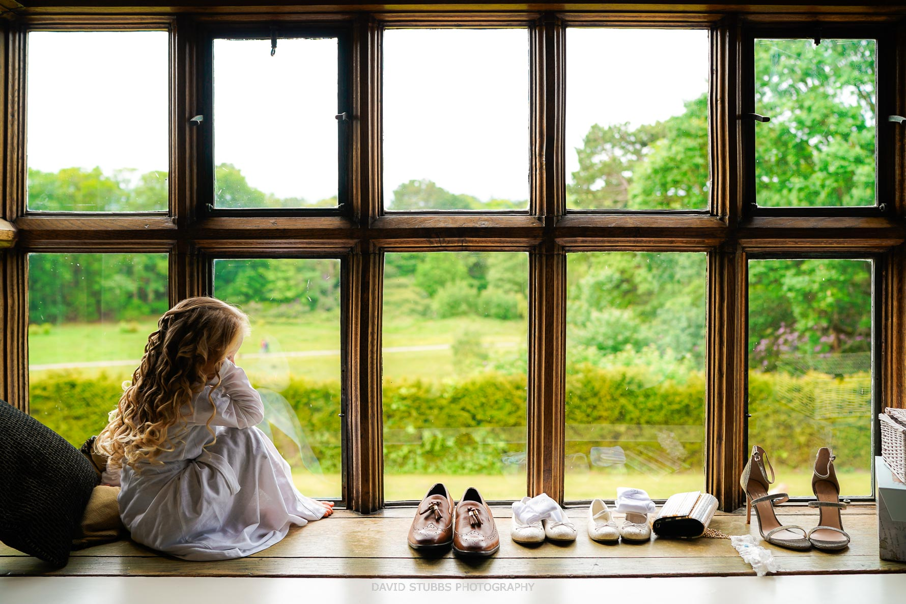 flower girl sits in large window light