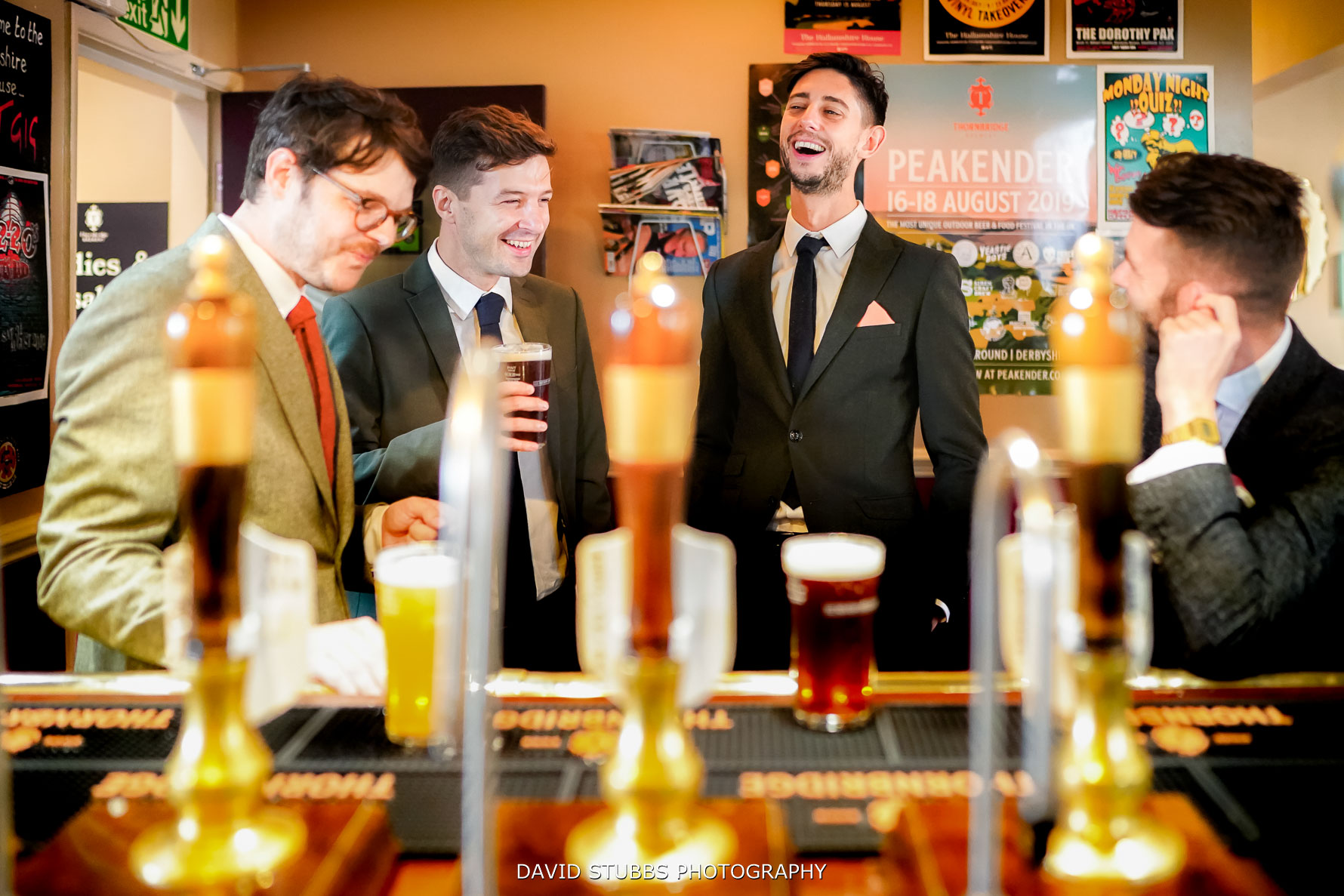 groomsmen being photographed having a drink