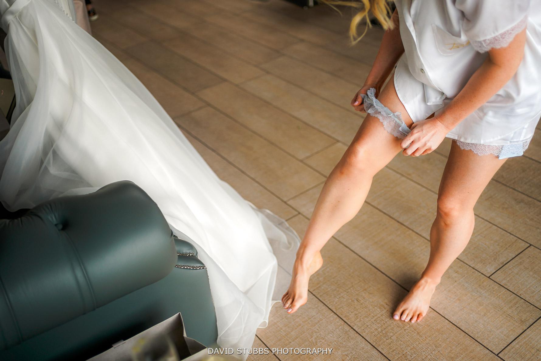 garter being placed on brides leg