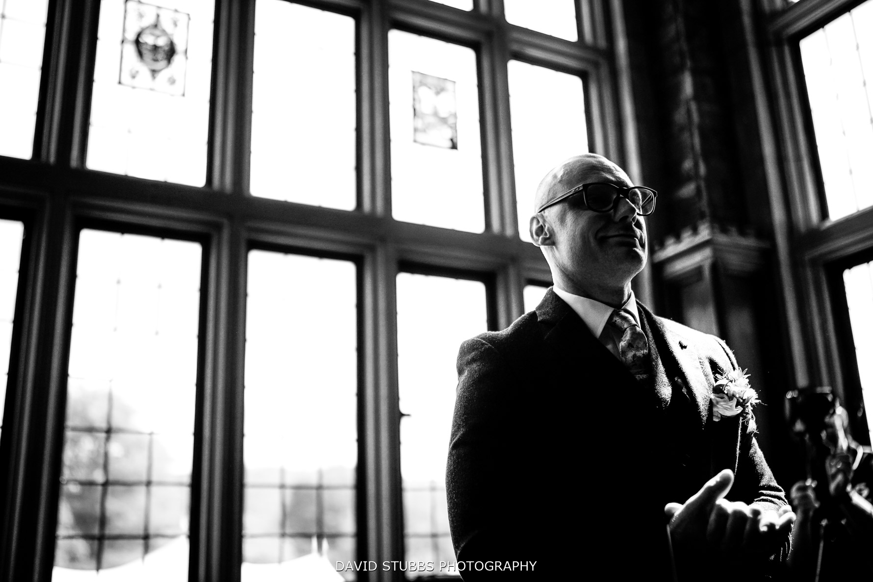 grooms waits in windown light low angle